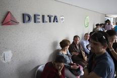 Customers wait their turn to be served in a line at the Delta airlines office in Caracas July 7, 2014. REUTERS/Carlos Garcia Rawlins