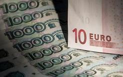 Банкноты российского рубля и евро в Москве 17 февраля 2014 года. Рубль в плюсе на спокойных торгах вторника за счет превалирования экспортных продаж в налоговый период над спросом на валюту в условиях её дефицита из-за западных санкций. REUTERS/Maxim Shemetov