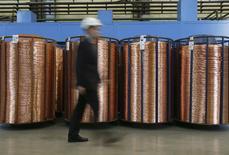Un hombre pasa entre barras de cobre en la planta Uralelektromed en Verkhnyaya Pyshma, Rusia, oct 17 2014. El cobre subió el jueves tras datos que mostraron que el sector empresarial de la zona euro tuvo un desempeño mejor del esperado, además de un leve crecimiento del sector manufacturero en China, uno de los mayores consumidores mundiales de metales. REUTERS/Maxim Shemetov