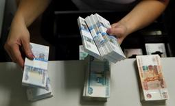 An employee of a bank counts rouble banknotes in Moscow September 2, 2014. Russian assets fell on Monday, with the rouble hitting a fresh record low against the dollar after Europe and the United States accused Russia of direct military involvement in Ukraine. REUTERS/Maxim Zmeyev (RUSSIA - Tags: BUSINESS POLITICS CIVIL UNREST CONFLICT)