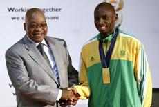 South Africa's President Jacob Zuma (L) congratulates medallist and long distance runner Mbulaeni Mulaudzi at the presidential guest house in Pretoria August 25, 2009. REUTERS/Siphiwe Sibeko