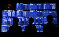 Personas observan una pantalla con distintas cotizaciones en la bolsa de Tokio. Imagen de archivo, 16 octubre, 2014.  Las bolsas de Asia subieron el miércoles a máximos de un mes, impulsadas por un sólido desempeño en Wall Street por el optimismo sobre las ganancias corporativas y las perspectivas de que la Reserva Federal de Estados Unidos reafirmará su voluntad de esperar durante un período prolongado antes de elevar las tasas de interés. REUTERS/Yuya Shino