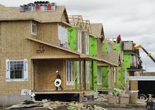 Construction workers work on building new homes in Calgary, Alberta, May 31, 2010.   REUTERS/Todd Korol