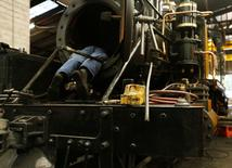 An engineer works inside the smokebox of a steam engine undergoing an overhaul in the Puffing Billy workshops at Belgrave Melbourne, October 20, 2014. REUTERS/Jason Reed