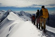 Roped up climbers leave the summit of Breithorn at 4,164 metres (13,661 feet) on the ridge marking the border with Switzerland (left) and Italy in the Alpine resort of Zermatt August 4, 2014. REUTERS/Denis Balibouse