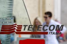 Personas pasan atrás de un logo de Telecom Italia en una casilla telefónica en Roma. Imagen de archivo, 28 agosto, 2014. Pequeños inversionistas de Telecom Italia pidieron el martes a la junta del grupo que considere una potencial fusión de su unidad brasileña TIM Participações SA con la local Grupo Oi SA.  REUTERS/Max Rossi