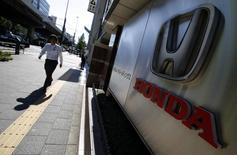 A pedestrian walks past a logo of Honda Motor Co outside the company's dealership in Tokyo October 28, 2014. REUTERS/Yuya Shino