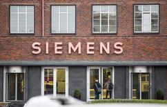 Personas entran a un edificio de Siemens en Berlín, 06 noviembre, 2014. El grupo de ingeniería alemán Siemens incumplió las expectativas de ganancias estructurales en su cuarto trimestre fiscal, afectado por unos cargos sobre unas turbinas de viento defectuosas que empujaron a su división de energía eólica a una pérdida.  REUTERS/Hannibal