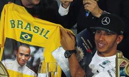Mercedes Formula One driver Lewis Hamilton of Britain receives a Brazil shirt printed with his photograph, during a media conference in Sao Paulo November 5, 2014. REUTERS/Paulo Whitaker