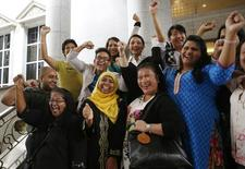 Activists celebrate overturning a sharia law against cross-dressing at the Appeals Court in the Palace of Justice in Putrajaya November 7, 2014. REUTERS/Olivia Harris