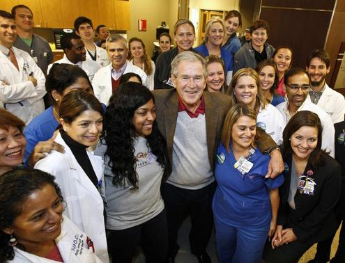 Former U.S. President George W. Bush (C) poses with caregivers in the Medical Intensive Care Unit at Texas Health Presbyterian Hospital in Dallas, Texas November 7, 2014.  REUTERS/Texas Health Presbyterian Hospital Dallas/Handout via Reuters