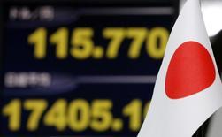 Флаг Японии на фоне экрана, отражающего курс иены к доллару США и значение индекса Nikkei, в трейдинговой компании в Токио 12 ноября 2014 года. Курс доллара к иене поднялся до семилетнего максимума на фоне ожиданий досрочных парламентских выборов в Японии. REUTERS/Toru Hanai