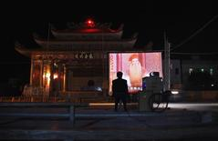 A man sits next to a mobile projector showing a Chinese opera film in front of the local theatre building in the village of Wukan in Lufeng county, Guangdong province December 21, 2011. REUTERS/David Gray