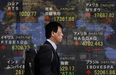 Мужчина у брокерской конторы в Токио 19 ноября 2014 года. Азиатские фондовые рынки снизились в среду под влиянием местных новостей. REUTERS/Yuya Shino