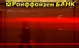 Вывеска на отделении Райффайзен Банка в Санкт-Петербурге 25 сентября 2014 года. Доналоговая прибыль Raiffeisen Bank International в России снизилась до 100 миллионов евро в третьем квартале 2014 года со 127 миллионов во втором квартале, так как обесценивание рубля перевесило хорошие операционные результаты. REUTERS/Alexander Demianchuk