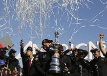Skipper James Spithill kisses the America's Cup with members of the Oracle Team USA after winning the overall title of the 34th America's Cup yacht sailing race over Emirates Team New Zealand in San Francisco, California September 25, 2013.       REUTERS/Robert Galbraith