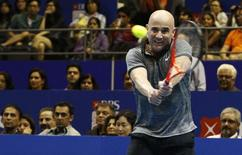 Singapore Slammers' Andre Agassi of the U.S. hits a return to Manila Mavericks' Mark Philippoussis of Australia during their men's singles match at the International Premier Tennis League (IPTL) in Singapore December 2, 2014. REUTERS/Edgar Su