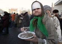 Женщина ест гречку в Санкт-Петербурге 27 января 2012 года. Инфляция в России за период с 25 ноября по 1 декабря составила 0,3 процента, третью неделю подряд, сообщил Росстат. REUTERS/Alexander Demianchuk