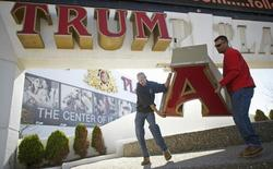 (L-R) Steven Nordaby and Tony Demidio, of Calvi Electric, remove the letter 'A' from the signage of Trump Plaza Casino in Atlantic City, New Jersey October 6, 2014. REUTERS/Mark Makela