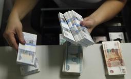Un trabajador de un banco cuenta billetes de rublos en Moscú. Imagen de archivo, 2 septiembre, 2014. El rublo cayó el viernes a un nuevo mínimo de casi 58 unidades por dólar, manteniendo un declive que según operadores llevó al banco central ruso a intervenir en el mercado luego de que una subida de las tasas no lograra contener la depreciación de la moneda. REUTERS/Maxim Zmeyev