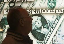 Иранец у пункта обмена валюты в Тегеране 3 января 2012 года. Курс доллара снижается к иене вслед за доходностью американских гособлигаций на фоне нежелания инвесторов рисковать. REUTERS/Morteza Nikoubazl