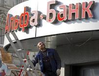 Рабочий смотрит на вывеску Альфа-банка в Москве 19 апреля 2013 года. Российские власти обсуждают пролонгацию субординированных кредитов, выданных в кризис 2008-2009 года, для ряда банков еще на 10-15 лет, сказал замминистра финансов РФ Алексей Моисеев. REUTERS/Sergei Karpukhin