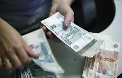 Un empleado de un banco cuenta billetes de rublos rusos en Moscú. Imagen de archivo, 2 septiembre, 2014. El rublo y los activos rusos se hundieron el lunes a nuevos mínimos entre temores a posibles nuevas sanciones de Estados Unidos por la crisis en Ucrania, los débiles precios del petróleo y apuestas a que la moneda seguirá cayendo. REUTERS/Maxim Zmeyev