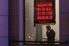 Мужчина говорит по телефону в здании на фоне вывески пункта обмена валюты в Москве 16 декабря 2014 года. Рубль лихорадит в начале биржевой сессии среды - его отрицательная динамика прерывалась резким восстановлением, в котором участники рынка не исключают и руку ЦБ, но также допускают и появление продаж экспортной выручки под уплату налогов.  REUTERS/Maxim Zmeyev