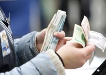 Уличный торговец пересчитывает купюры в Минске 5 октября 2013 года. Белорусский президент Александр Лукашенко сказал, что Белоруссия не будет девальвировать национальную валюту, несмотря на падение курса российского рубля, и потребовал перейти на расчеты с Россией в долларах и евро, передало государственное агентство БелТА. REUTERS/Vasily Fedosenko