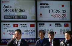 Personas pasan frente a una pantalla electrónica que muestra el Nikkei y otros índices económicos en Tokio. Imagen de archivo, 19 diciembre, 2014. Las bolsas de Asia seguían el lunes la dirección de un repunte en Wall Street y comenzaban en un buen pie una semana acortada por el feriado de Navidad, al tiempo que los precios del petróleo rebotaban y el euro tocaba un nuevo mínimo de dos años frente al dólar. REUTERS/Issei Kato