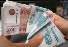 Сотрудник магазина пересчитывает рублевые купюры в Красноярске 26 декабря 2014 года. Рубль начал торги понедельника снижением к доллару и евро, отыгрывая уход нефтяных котировок ниже $60 и игнорируя завершение налоговых платежей. REUTERS/Ilya Naymushin