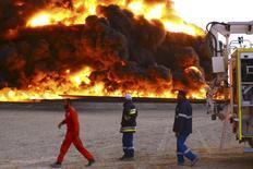 Bomberos intentan apagar un incendio en el tanque petrolero de Es Sider. Imagen de archivo, 26 diciembre, 2014. La producción de petróleo de Libia se ha reducido aún más debido a un incendio en depósitos de crudo de un importante puerto, que hizo que los precios mundiales suban y aumente el forado en las reservas de divisas de ese país. REUTERS/Stringer