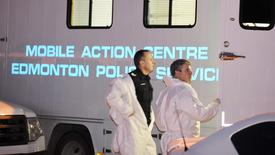 Investigators meet at one of three crime scenes where seven people were found dead, in north Edmonton, Alberta, December 30, 2014. REUTERS/Dan Riedlhuber