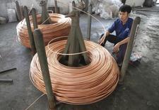 Un trabajador revisa un cable de cobre en la fábricaTruong Phu en Hai Duong, Vietnam, nov 2 2013. Los precios del cobre cerraron el 2014 con pérdidas de un 14 por ciento, su mayor declive anual en tres años, debido a las preocupaciones de que un superávit de suministros afectará al mercado el próximo año en momentos en que el crecimiento económico en China se desacelera. REUTERS/Kham