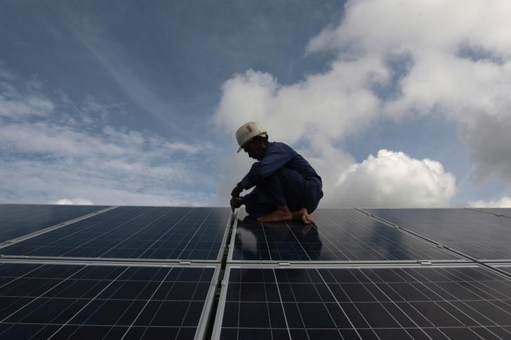 A worker adjusts solar panels at a park on the outskirts of Havana September 24, 2013. REUTERS/Stringer/Files