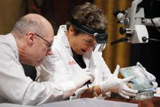 Executive Director of the Massachusetts Archives, Michael Comeau, and MFA conservator Pam Hatchfield open a time capsule, which was placed under a cornerstone of the State House in 1795, at the Museum of Fine Arts, Boston, Massachusetts, January 6, 2015. REUTERS/Brian Snyder
