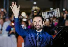 """Cast member John Travolta waves upon arrival for the """"The Forger"""" gala during the Toronto International Film Festival (TIFF) in Toronto, in this file photo taken September 12, 2014. REUTERS/Mark Blinch/Files"""