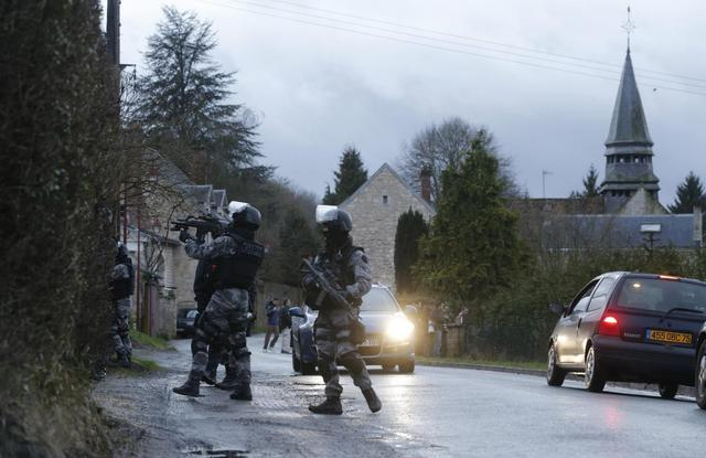 Members of the French GIPN intervention police forces secure a neighbourhood in Corcy, northeast of Paris January 8, 2015.  REUTERS/Christian Hartmann