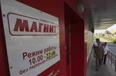 Люди у входа в магазин Магнит на окраине Москвы 1 августа 2012 года. Крупнейший российский ритейлер Магнит увеличил продажи в декабре 2014 года на 37,3 процента в годовом выражении до 87,36 миллиарда рублей, сообщила компания, в целом за год нарастившая выручку на 31,6 процента до 762,7 миллиарда рублей. REUTERS/Sergei Karpukhin