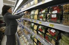 Работник московского супермаркета Ашан раскладывает продукты на полках. 28 ноября 2014 года. Рост потребительских цен в России в прошедшем году на уровне 11,4 процента был максимальным с кризисного 2008 года, когда инфляция составляла 13,3 процента, на фоне взаимных внешнеторговых санкций и ослабления рубля. REUTERS/Sergei Karpukhin