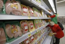 Сотрудники раскладывают продукцию на полках магазина Ашан в Москве 28 ноября 2014 года. Индекс потребительских цен в РФ за период с 1 по 12 января 2015 года вырос на 0,8 процента, сообщил Росстат. REUTERS/Sergei Karpukhin