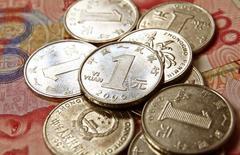 Yuanes chinos vistos en una fotografía tomada en Beijing. Imagen de archivo, 8 febrero, 2011.  Tras un aumento en el interés por el yuan el año pasado, la moneda china avanza hacia las grandes ligas de las divisas, con volúmenes en operaciones que se comparan más con los del euro, la libra, el dólar australiano y el franco suizo que con los de sus pares de mercados emergentes.  REUTERS/Petar Kujundzic