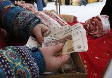 """Продавщица пересчитывает купюры на рынке в Красноярске 14 января 2015 года. Рубль торгуется в плюсе на малоактивной сессии понедельника - поддержкой российской валюте выступает остановившая глубокое падение нефть, налоговый период и госмониторинг экспортной выручки, перевесившие в условиях низкой ликвидности обострение ситуации на востоке Украины и возможность понижения кредитного рейтинга РФ до """"мусорного"""" статуса. REUTERS/Ilya Naymushin"""
