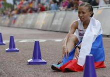Russia's Olga Kaniskina sits on the ground after finishing second in the women's 20km race walk final at the London 2012 Olympic Games at The Mall August 11, 2012. REUTERS/Laszlo Balogh