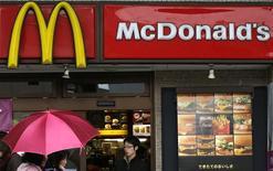 Personas pasan frente un local de McDonalds en Tokio. Imagen de archivo, 16 diciembre, 2014. McDonald's Corp, la mayor cadena de restaurantes del mundo, reportó una caída del 7,3 por ciento de sus ventas trimestrales, en momentos en que lucha por recuperarse de un escándalo alimentario en China y se ve afectada por la competencia en Estados Unidos. REUTERS/Issei Kato