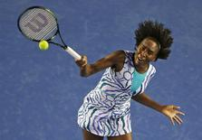 Venus Williams of the U.S. jumps to hit a return to Agnieszka Radwanska of Poland during their women's singles fourth round match at the Australian Open 2015 tennis tournament in Melbourne January 26, 2015. REUTERS/Carlos Barria