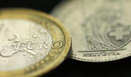 Монеты евро и швейцарского франка. Манчестер, 16 января 2015 года. Швейцарский франк в четверг снизился на два процента к евро и доллару на фоне возобновившихся слухов об интервенции Национального банка Швейцарии. REUTERS/Phil Noble