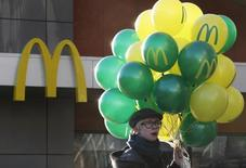 A customer holds balloons outside a McDonald's restaurant on the day of its reopening in central Moscow November 19, 2014. REUTERS/Sergei Karpukhin