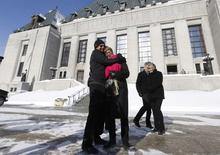 Lee Carter (2nd L) gets a hug from her husband Hollis Johnson outside the Supreme Court of Canada in Ottawa February 6, 2015. Carter's mother, Kay Carter, traveled to Switzerland to end her life in 2010. REUTERS/Chris Wattie