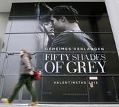 A pedestrian walks past an advertising placard for the movie 'Fifty Shades of Grey' which will be screened at the upcomming 65th Berlinale International Film Festival in Berlin February 4, 2015.   REUTERS/Fabrizio Bensch